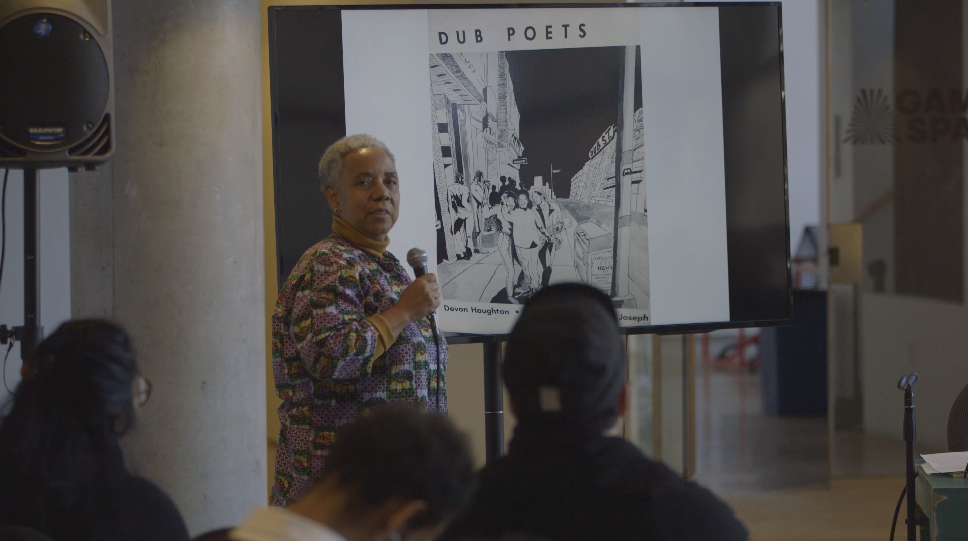 "A photograph of Lillian Allen holding a microphone during a presentation. Television monitor behind her showcasing a black and white drawing of three people and the text ""Dub Poets"" above."